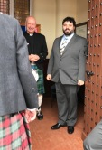 The groom and minister greeting guests at the church door