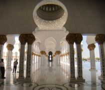 Gold leaf abounds on the exterior walkways of the Sheikh Zayed Grand Mosque, with large intricate domes along the way.