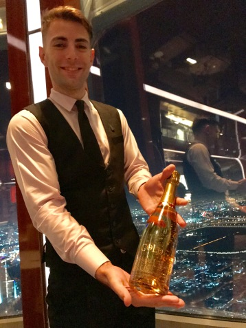 Our excellent waiter Alex offers a drink containing GOLD at At.mosphere, Burj Khalifa.