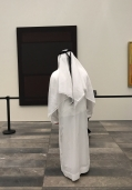 A man in white thobe contemplates a dark Rothko at the Louvre Abu Dhabi.
