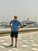Jimmy standing in the Port Rashid marina with the QE2 in the background.